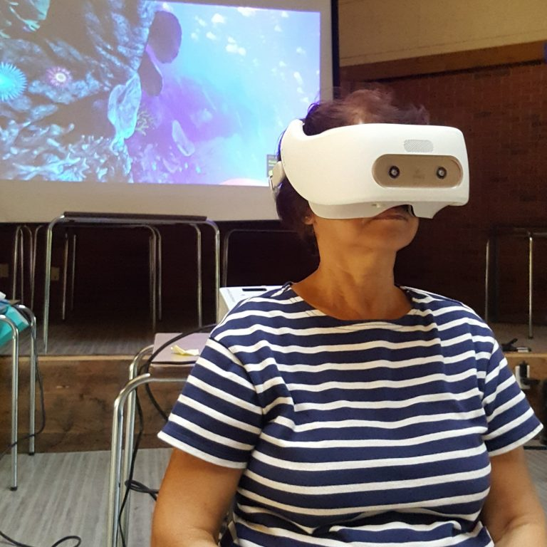 An older lady viewing virtual reality in a HTC Vive Focus.
